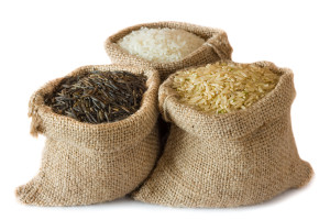 Three kinds of rice in small burlap bags isolated on white background